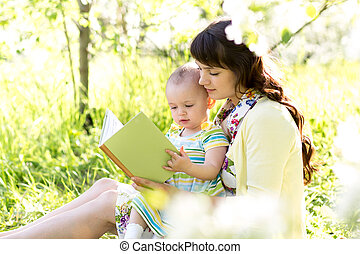 mother reading a book to kid outdoors