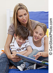 Mother reading a book with her daughter and son