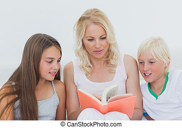 Mother reading a story to her children