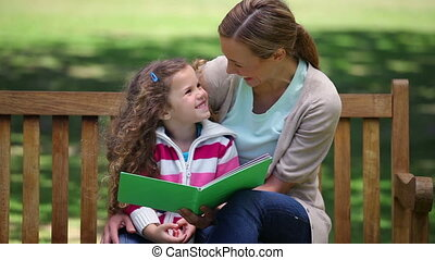 Mother reading a story to her daughter on a bench in a park