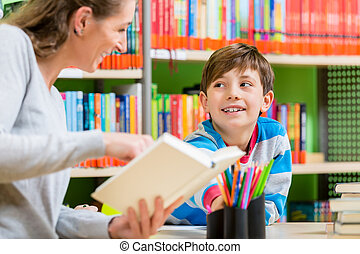 Mother reading book from library to her son