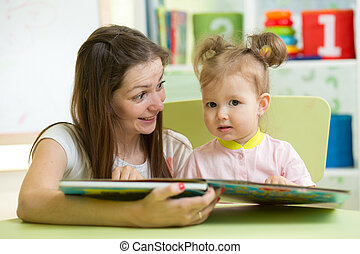 Mother reading book her child in nursery
