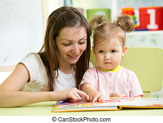 Mother reading book her kid daughter at table