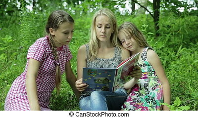 Mother reading book their daughters in park