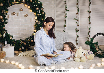 mother reading book to her little cute daughter near Christmas tree