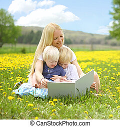Mother Reading Book to Young Children Outside