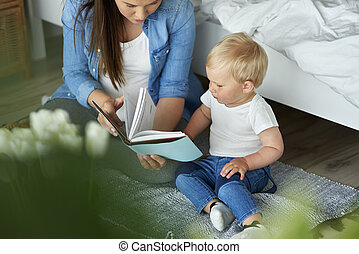 Mother reading book with her toddler son