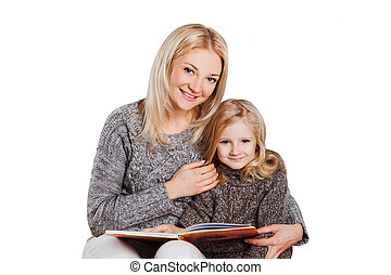 Mother reading book with young daughter