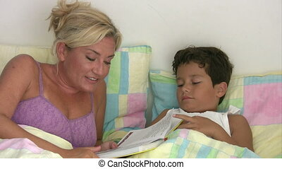 Mother reading to son in bed