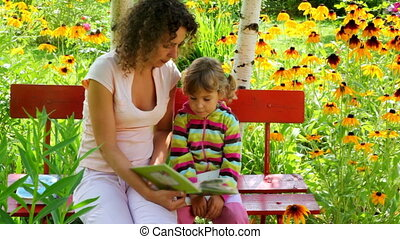 mother reading with daughter on the bench in the yard