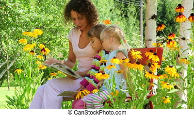 mother reading with two girls on the bench in the yard