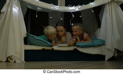 mother reads a bedtime story for children before going to...