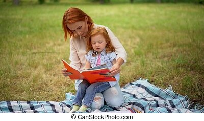 Mother reads a book with her daughter in the park.
