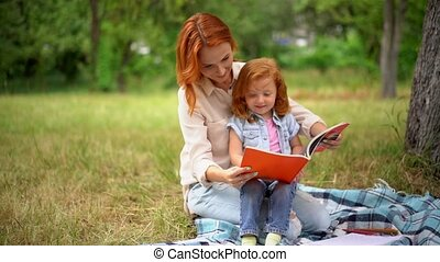 Stylish Woman Inn Casual Cloth Reads A Red Book With Her Little Daughter Witting On Her Laps In The Park. Family Concept