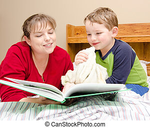 Mother reads bedtime story to boy
