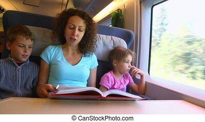 Mother reads book for children boy and girl when they travel
