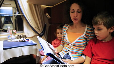 Mother reads book to son and daughter sitting in coupe riding train