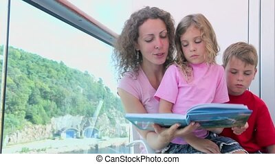Mother reads book with kids at balcony on ship