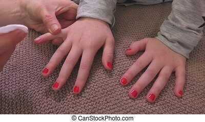 Mother removes nail varnish from daughter hand