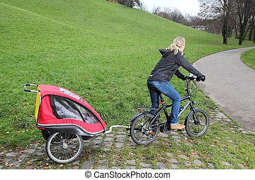 Mother riding a E-Bike with child trailer