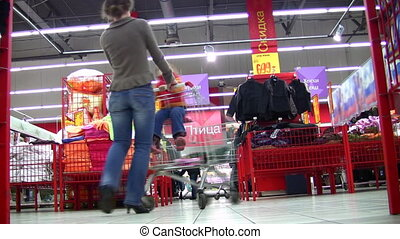 mother rotates child in shopping cart in shop