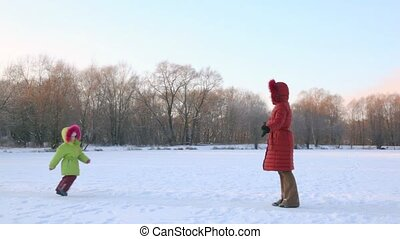 mother rotates with her daughter in snowfield