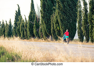 Mother runner with baby stroller jogging at sunset landscape
