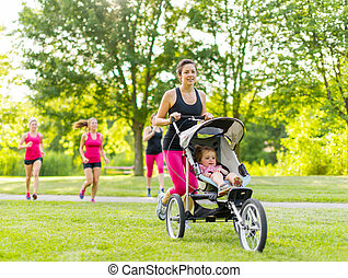Mother running in the park - Woman pushing her little girl ...