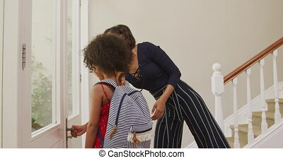 African American woman and her daughter standing in the hall, saying goodbye before setting off for school, in slow motion.