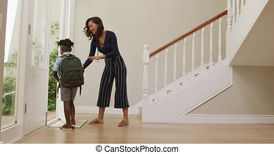 African American woman and her son standing in the hall, saying goodbye before setting off for school, in slow motion.