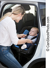 Mother seating her baby in car safety seat