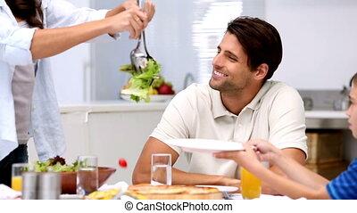 Mother serving salad at dinner