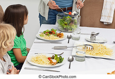 Mother serving salad to her childre