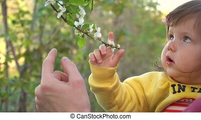 Mother show to baby flowers on trees in slow motion
