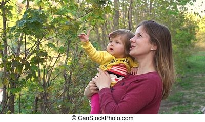 Mother show to baby flowers on trees in spring