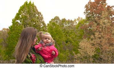 Mother showing and telling her baby autumn in the park