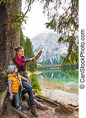Mother showing baby something while on lake braies in south tyro