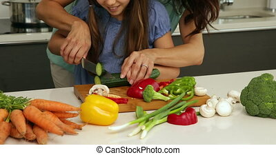 Mother showing her daughter how to chop vegetables at home...