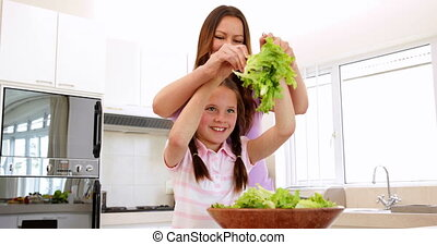 Mother showing her daughter how to toss salad