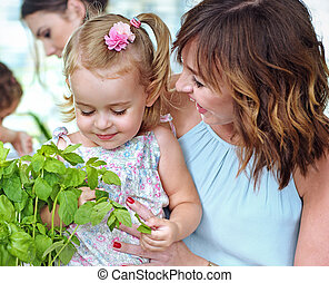 Mother showing her daughter the fresh herbs