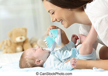 Mother showing new shoes to her baby
