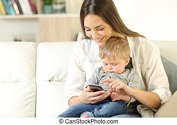 Mother showing smart phone content to his baby son