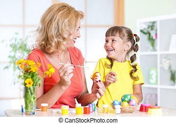 Mother showing to her child how to paint  Easter eggs