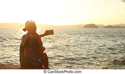 mother shows photos to daughter at sunset