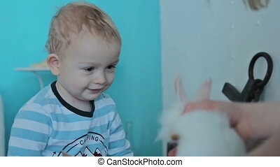 Mother shows white rabbit for her son