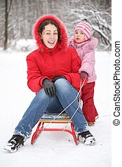 mother sits on sled in park with child at winter