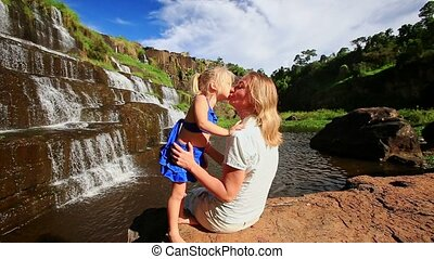 Mother Sits on Stone Plays with Little Girl by Waterfall Pongour