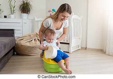 Mother sitting her baby on chamber pot