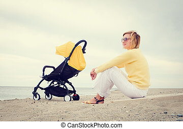 Mother sitting on beach by the sea
