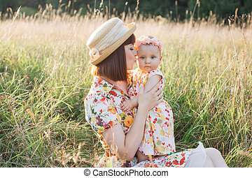 mother sitting on grass in summer field, with cute child girl in her arms, gently kissing baby cheek